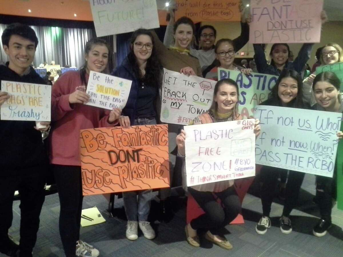 Students from Greenwich High School hold up signs in support of the plastic bag ban at the RTM meeting on Monday night.