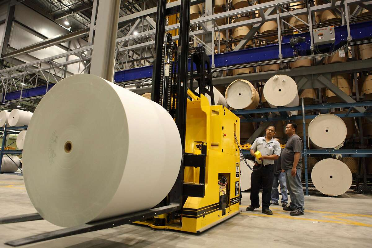 Workers prepare to guide a forklift with newsprint to feed a printing press at the Fremont plant where The Chronicle has been printed since 2009.