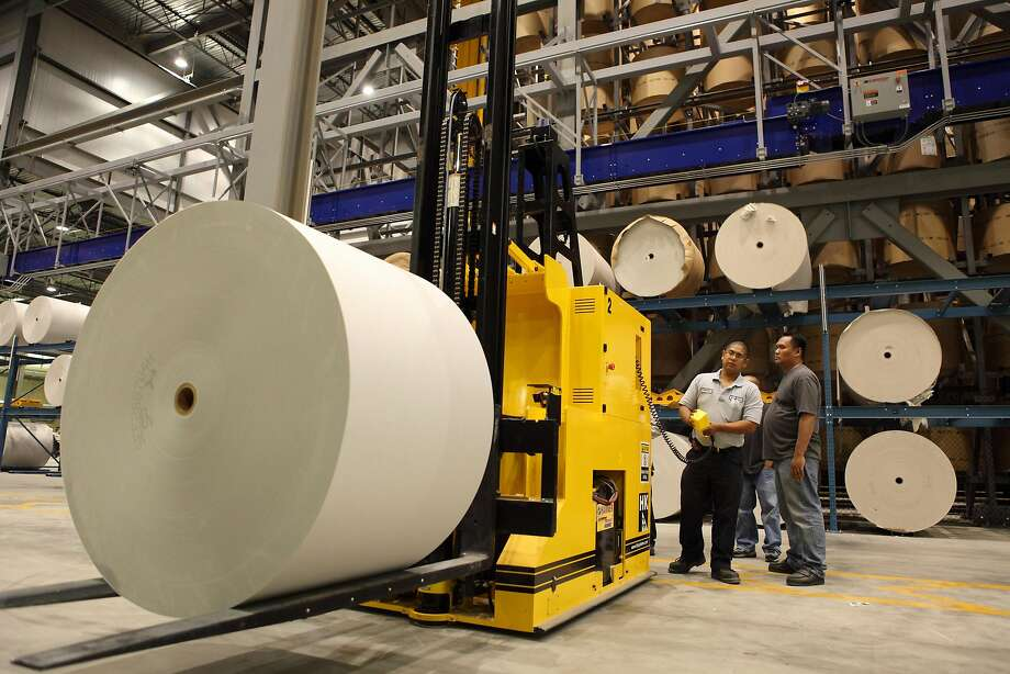 Workers prepare to guide a forklift with newsprint to feed a printing press at the Fremont plant where The Chronicle has been printed since 2009. Photo: Carlos Avila Gonzalez / The Chronicle 2009