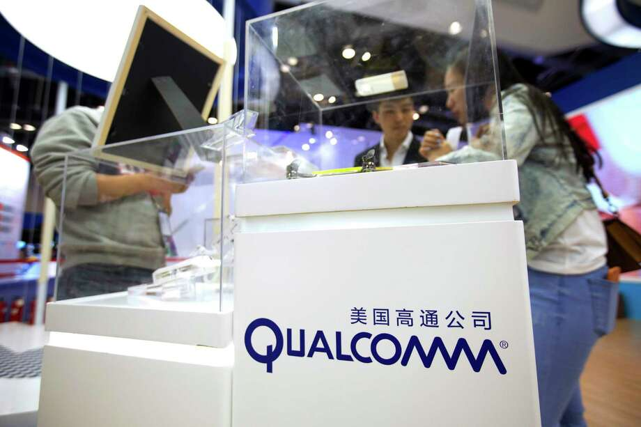 FILE - In this Thursday, April 27, 2017, file photo, visitors look at a display booth for Qualcomm at the Global Mobile Internet Conference (GMIC) in Beijing. On Monday, March 12, 2018, President Donald Trump blocked Singapore-based Broadcom's takeover of U.S. chipmaker Qualcomm on national security grounds. (AP Photo/Mark Schiefelbein, File) Photo: Mark Schiefelbein / Copyright 2017 The Associated Press. All rights reserved.