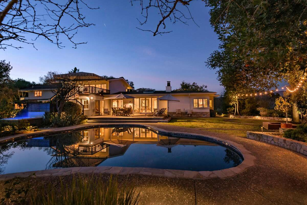 The backyard of the Glen Ellen country estate includes an irregularly shaped pool and wood deck.