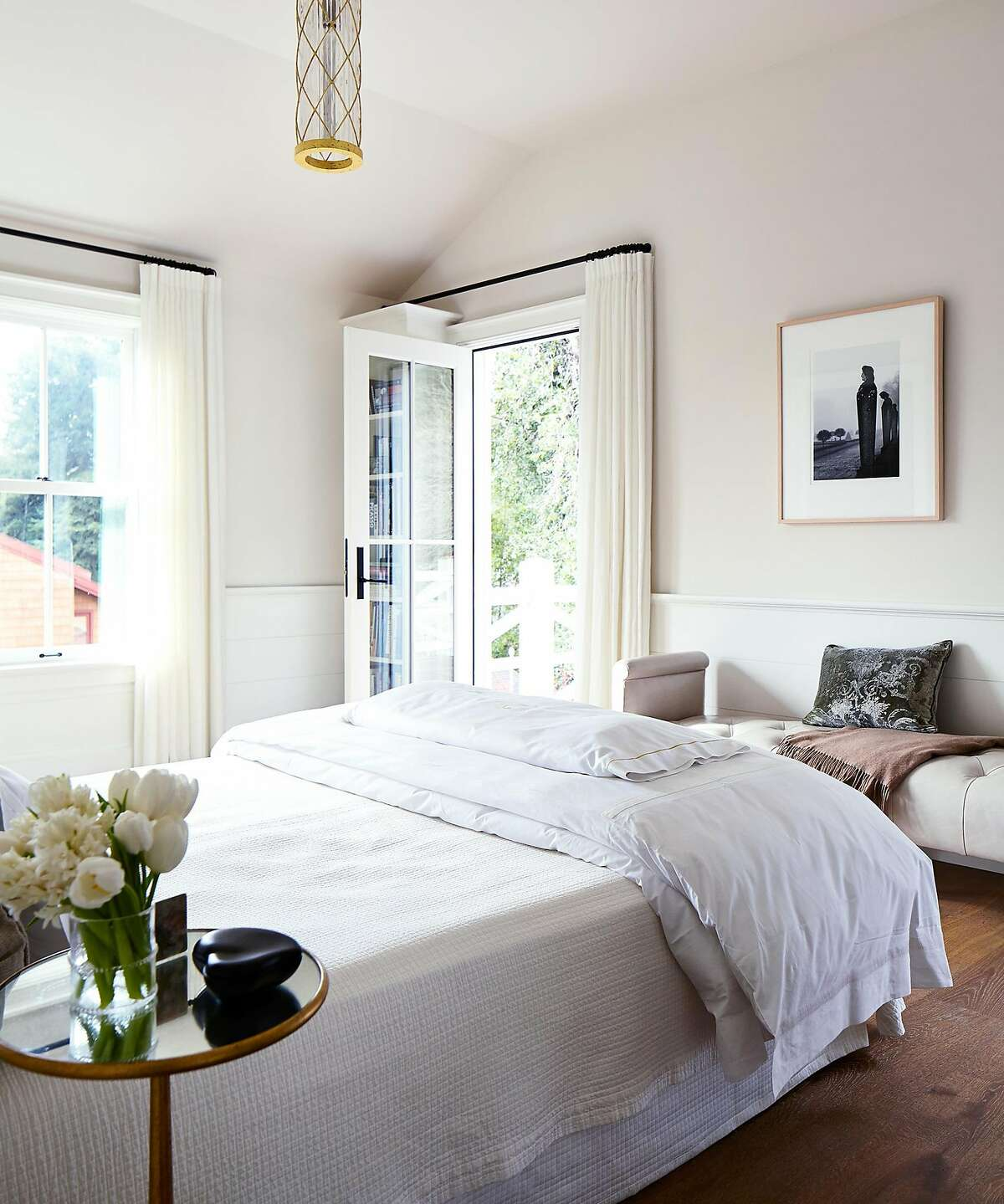 This Mill Valley bedroom opens to the outdoors and features custom lighting and window treatments.�
