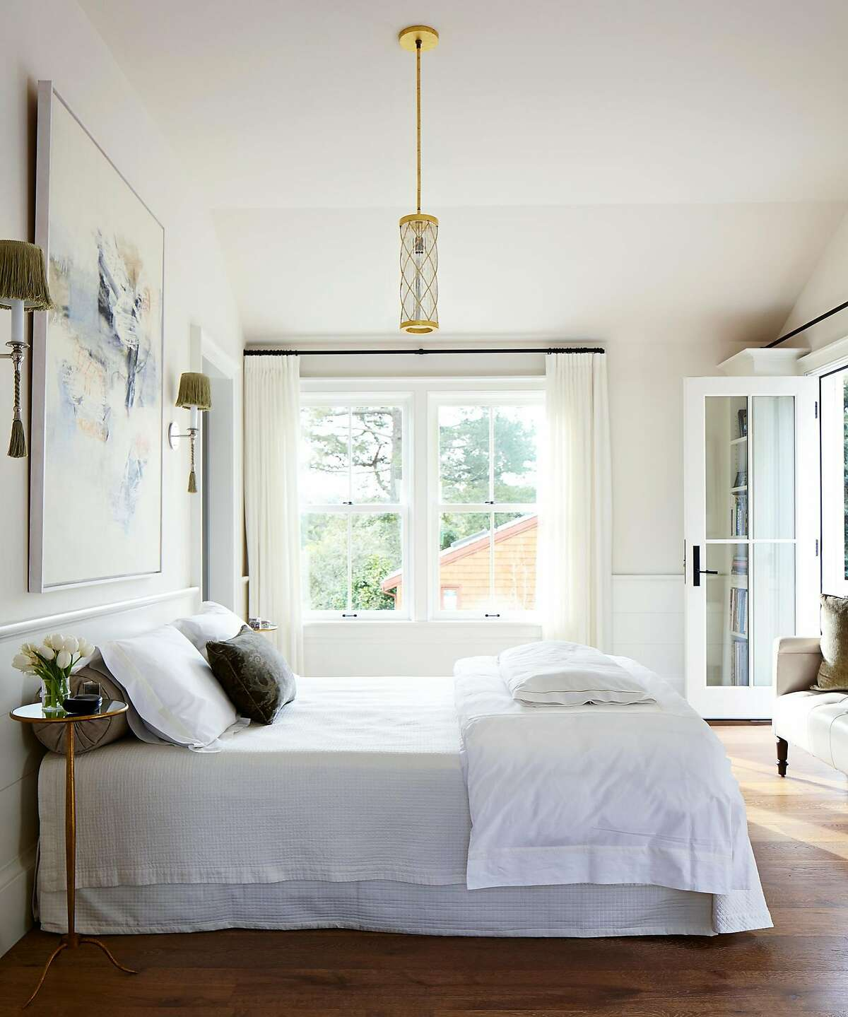 Wainscoting and hardwood flooring provide complementary classical finishes to this bedroom in Mill Valley.�