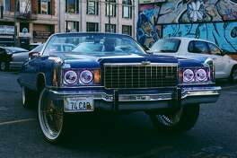Oakland Museum of California presents �Respect: Hip-Hop Style & Wisdom�:�DropReg, President of the East Bay Chevs group, in his ride during a video shoot in downtown Oakland. Image courtesy of the artist, Amanda Sade.