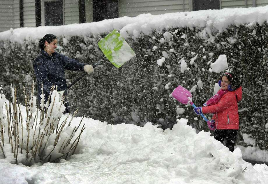 Kim Lemak and daughter Meredith, 6, hurl shovels full of snow at each other while sclearing their driveway on Cleveland Street in Danbury during Tuesday's snowfall, March 13, 2018. Kim, a teacher in Norwalk and Meredith, were home due to a school snowday Tuesday. Photo: Carol Kaliff / Hearst Connecticut Media / The News-Times