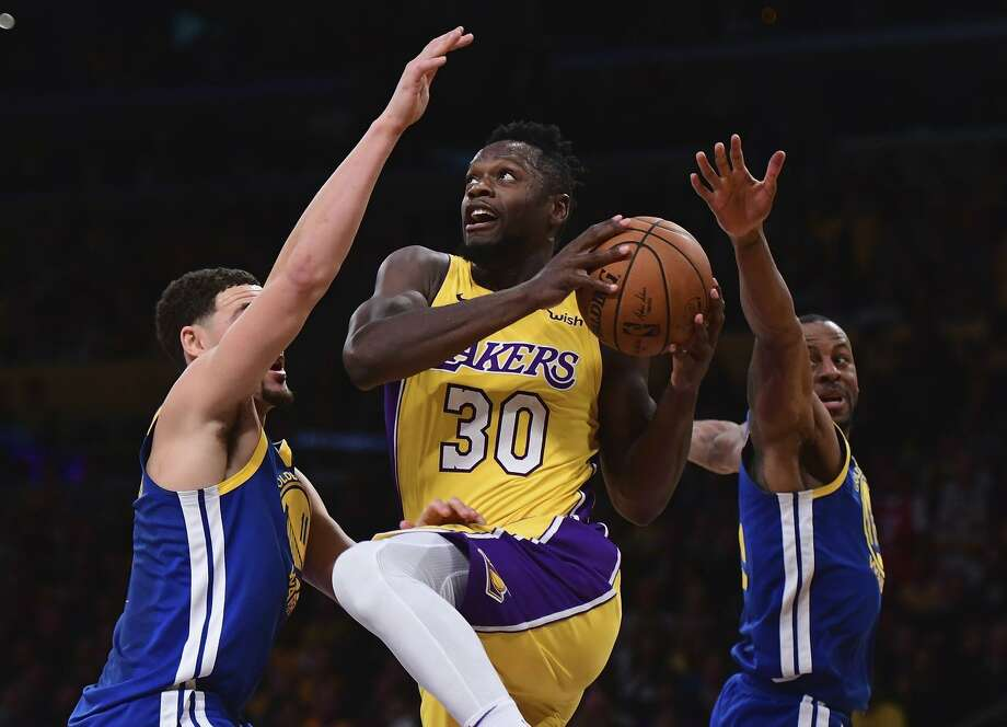 Julius Randle #30 of the Los Angeles Lakers drives between Klay Thompson #11 and Andre Iguodala #9 during a 116-114 Warrior overtime win at Staples Center on December 18, 2017 in Los Angeles, California. Photo: Harry How / Getty Images / 2017 Getty Images