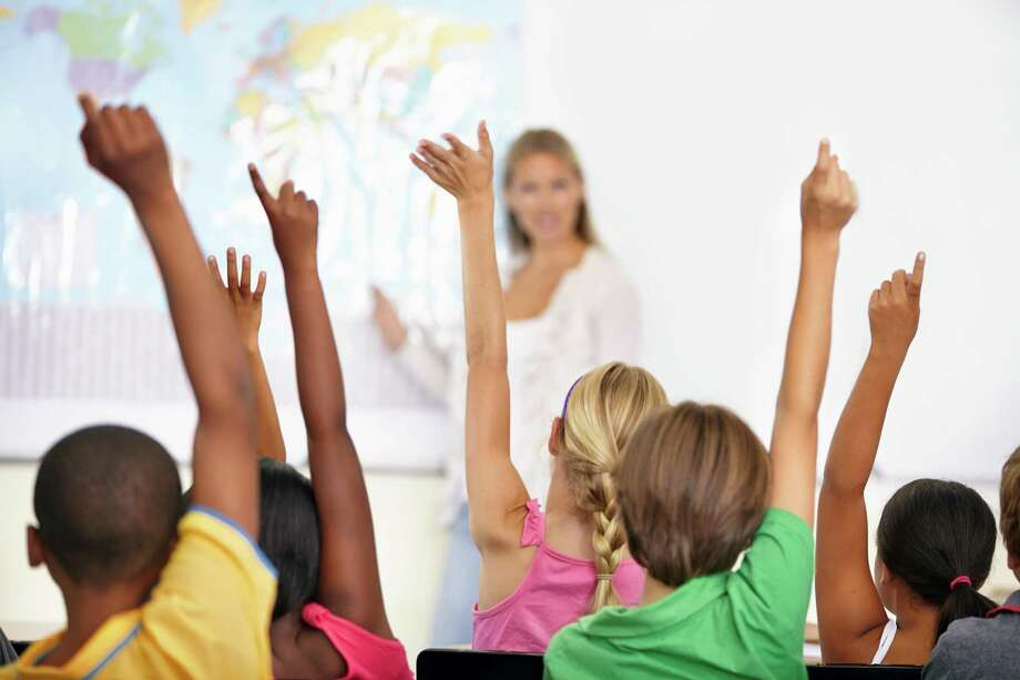 A teacher with a class full of eager students with their hands up Photo: PeopleImages, Contributor / Getty Images / online_yes