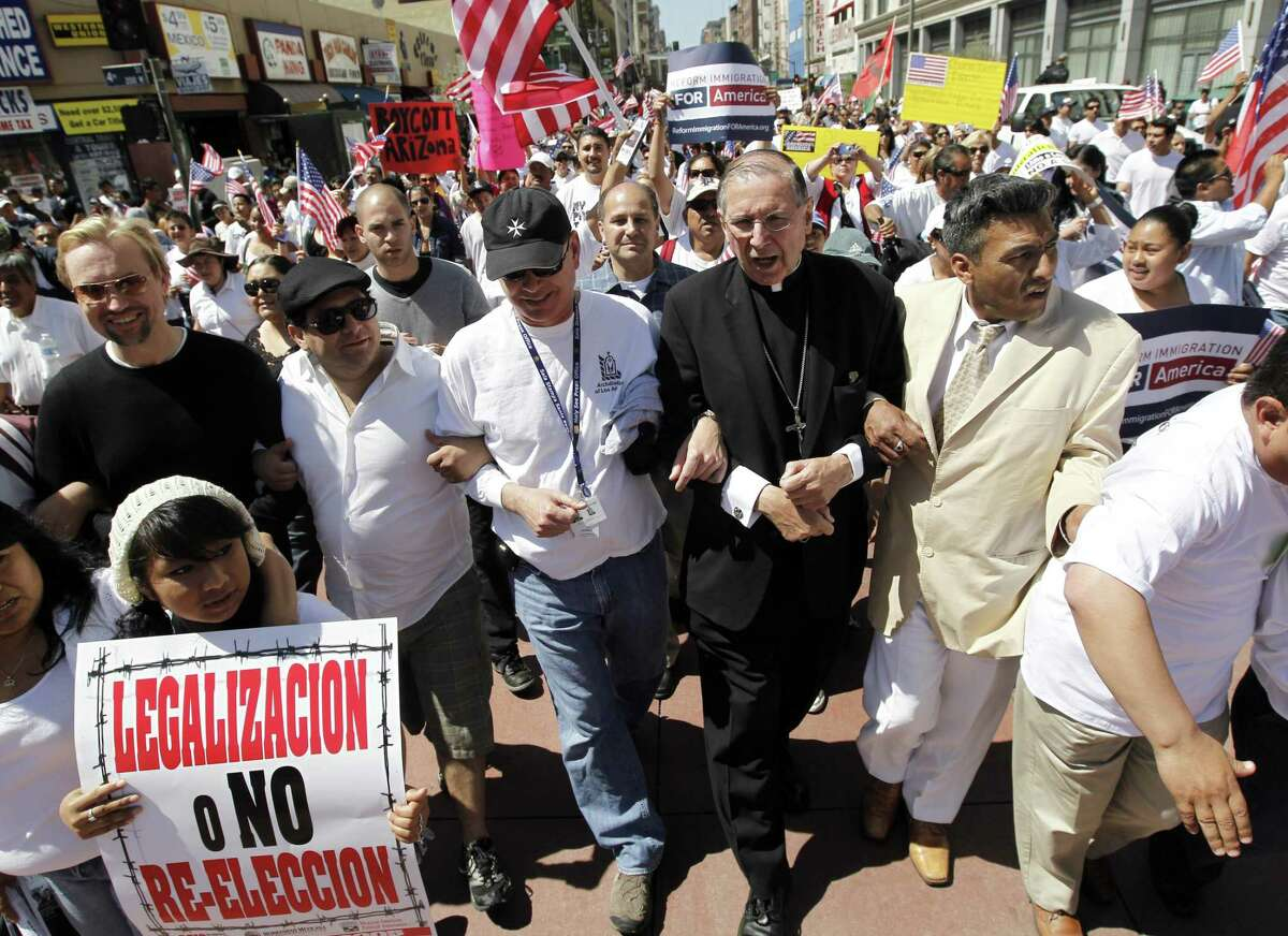 Cardinal Roger Mahony of the Roman Catholic Archdiocese of Los Angeles marches arm-in-arm with some of tens of thousands of demonstrators marching for reform of federal immigration law and to protest against Arizona's controversial new immigration law, in downtown Los Angeles Saturday, May 1, 2010. (AP Photo/Chris Carlson)