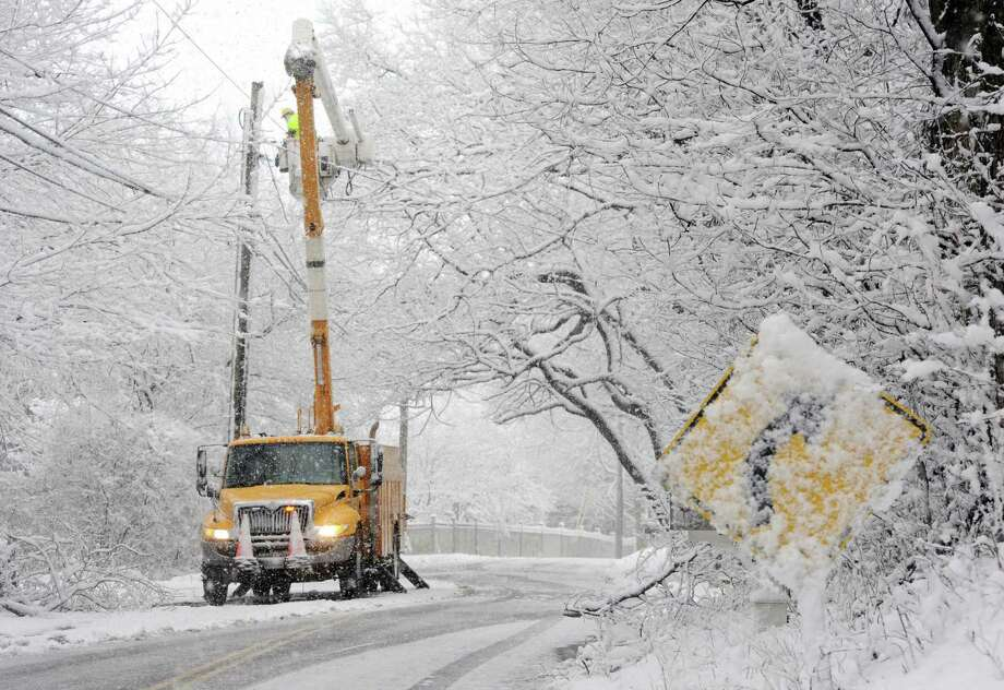 A UI crew works to restore power to homes on Hill Farm Road in Fairfield, Conn., after they lost power on Tuesday, March 13, 2018. After the region wrapped up recovery from last Wednesday's treacherous snowstorm that left about 160,000 in Connecticut in the dark, the third storm in less than two weeks hit New England on Tuesday, leaving some areas of Connecticut with nearly 11 inches of snow and others with barely a dusting.  Fairfield County totals ranged between just under an inch along the coast to 10.8 inches in Newtown, the National Weather Service reported. In New Haven County, totals started around less than half an inch in New Haven and were highest in Seymour at 4.5 inches.  New Jersey snowfall accumulations were between less than half an inch and 3.5 inches. In New York, Nassau County saw between 1.6 to 6.5 inches, Orange County had between 3.3 and 5.5 inches and Westchester got between 3.1 and 5.2 inches. Boston reported 8.5 inches of snow, but several parts of Massachusetts received more than a foot.  State police reported, between 4 a.m. and 4 p.m., troopers responded to 810 calls for service, 170 motorist assists, 75 accidents without injuries, two accidents with injuries and zero fatalities. Photo: Cathy Zuraw / Hearst Connecticut Media / Connecticut Post