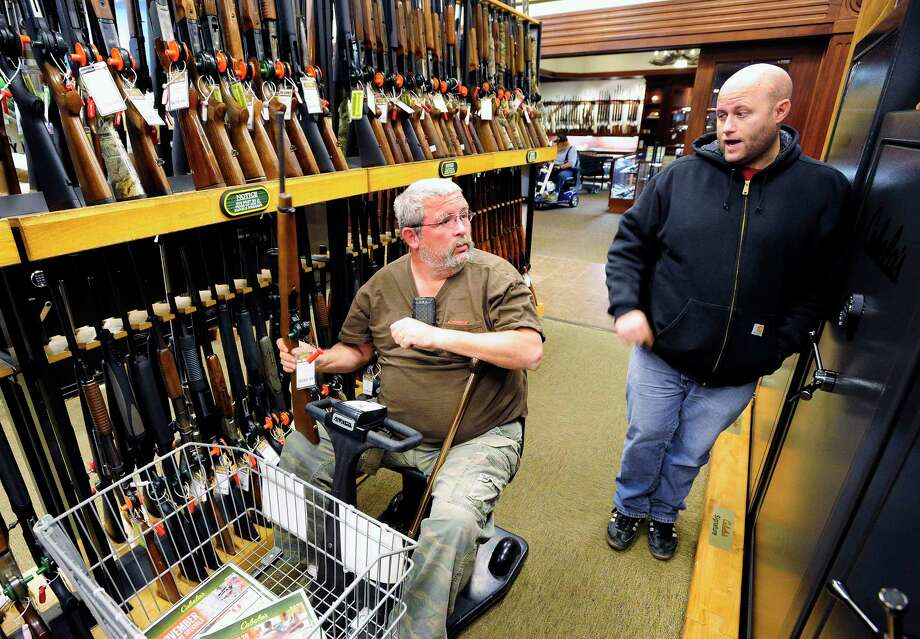 FILE- In this Nov. 10, 2014, file photo, Jerry Lyons, left, talks with Pat Ison at the Cabela's store in Dundee, Mich. Several outdoor chains, including Bass Pro Shops, Cabela's, Gander Outdoors and Academy Sports, continue to sell assault-style rifles online and in stores as part of their mix of hunting equipment. The decision is in stark contrast to Dick's Sporting Goods, which recently banned sales of assault rifles, and Walmart, which stopped carrying assault rifles in 2015 but says it will no longer sell guns or ammunition to anyone under 21. (Daniel Mears/Detroit News via AP, File) Photo: Daniel Mears / Detroit News