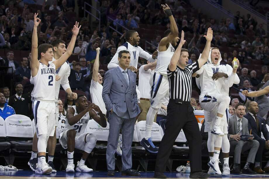 PHILADELPHIA, PA - FEBRUARY 21: Collin Gillespie #2, Dhamir Cosby-Roundtree #21, Mikal Bridges #25, Phil Booth #5 and Donte DiVincenzo #10 of the Villanova Wildcats celebrate from the bench while head coach Jay Wright looks on after a three-point basket by Denny Grace in the second half against the DePaul Blue Demons at the Wells Fargo Center on February 21, 2018 in Philadelphia, Pennsylvania. The Villanova Wildcats defeated the DePaul Blue Demons 93-62. (Photo by Mitchell Leff/Getty Images) Photo: Mitchell Leff, Getty Images