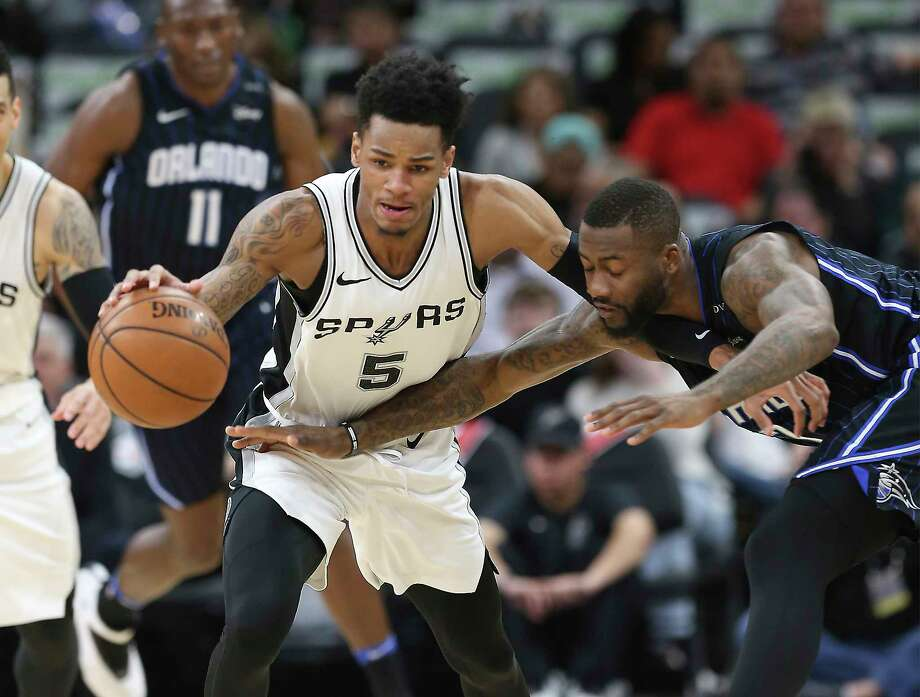 Spurs' Dejounte Murray (05) gets a steal against Orlando Magic's Jonathon Simmons (17) during their game at the AT&T Center on Tuesday, Mar. 13, 2018. Photo: Kin Man Hui, San Antonio Express-News / ©2018 San Antonio Express-News