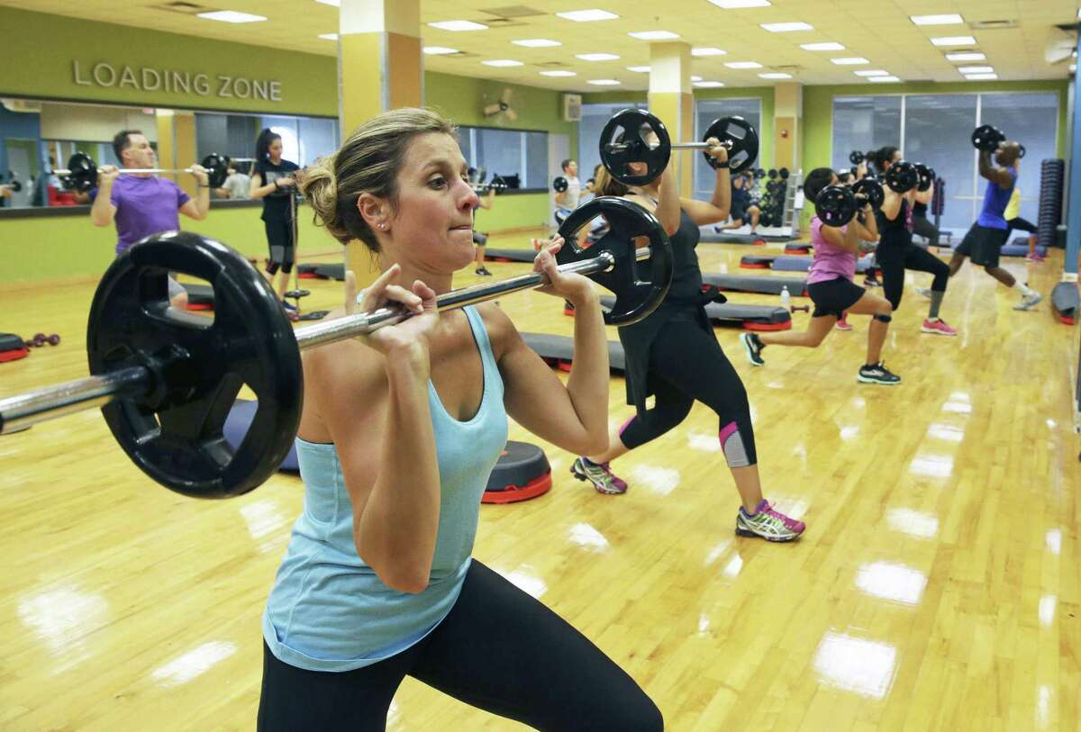 Emily Noll lifts weights during a group class at Gold's Gym at the Quarry on June 8, 2017.