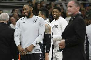 Spurs' Kawhi Leonard (02) laughs while joking with teammate Rudy Gay during a timeout in the game against the Orlando Magic at the AT&T Center on Tuesday, Mar. 13, 2018. Spurs defeated the Magic, 108-72. (Kin Man Hui/San Antonio Express-News)