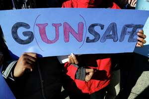 James Ferris High School freshmen Diamond Bryant, left, and James Williams interlock arms while holding a sign during a student walkout, Wednesday, March 14, 2018, in Jersey City, N.J. Students across the country participate in walkouts Wednesday to protest gun violence, one month after the deadly shooting inside a high school in Parkland, Fla.