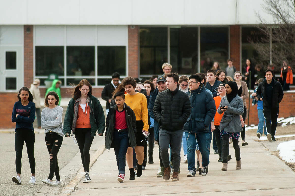 Students participate in a school walk out in protest of gun violence on Wednesday, March 14, 2018 at Dow High School. Protests were organized by high school students across the country on Wednesday, one month after 17 people were killed in a shooting at a high school in Parkland, Florida. (Katy Kildee/kkildee@mdn.net)