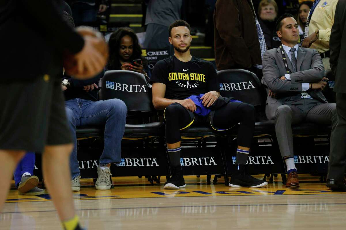From the bench, Golden State Warriors guard Stephen Curry (30) watches teammates practice before the start of an NBA basketball game between the Golden State Warriors and the Denver Nuggets at Oracle Arena on Saturday, Dec. 23, 2017 in Oakland, Calif. Curry is injured and did not play.
