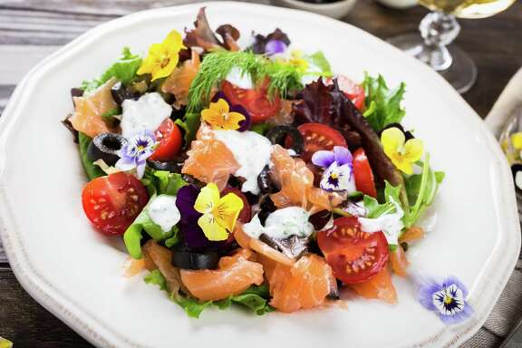 Fresh salad with smoked salmon, black olives, cherry tomatoes and edible flowers.