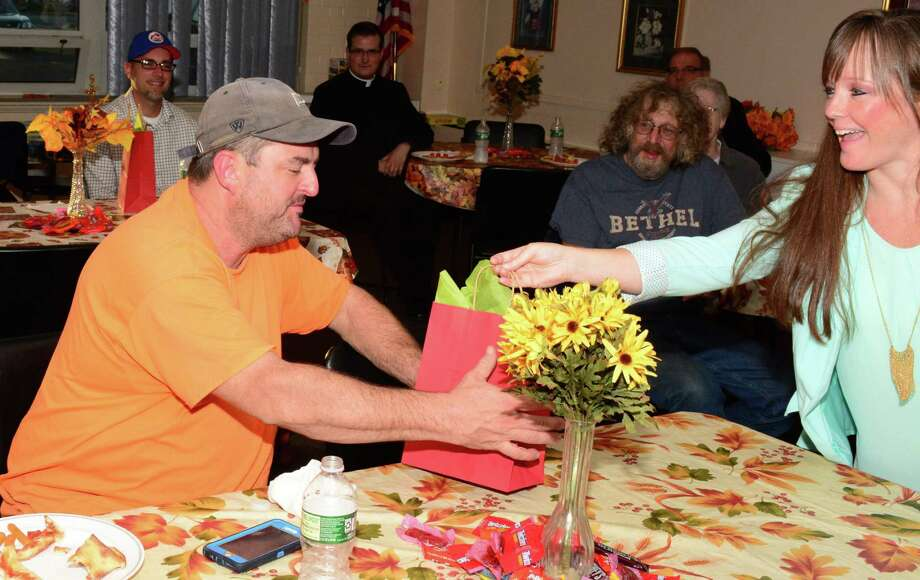 File photo of Megan Alworth-Khazadian, social worker for the town of Bethel, giving a goody bag with donations to Paul Gorman who was affected by the fire that happened over the summer on Greenwood Avenue. The event took place at the Senior Center in Bethel on Wednesday October 4, 2017. The Social Services Department is collecting items for Easter baskets for families in need. Photo: Lisa Weir / For Hearst Connecticut Media / The News-Times Freelance