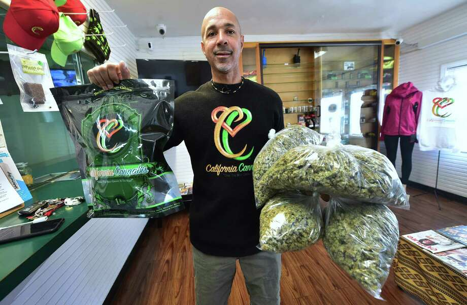 Cannabis entrepreneur Virgil Grant carries bags of medical marijuana at a dispensary he runs in Los Angeles. Photo: Getty Images / AFP or licensors