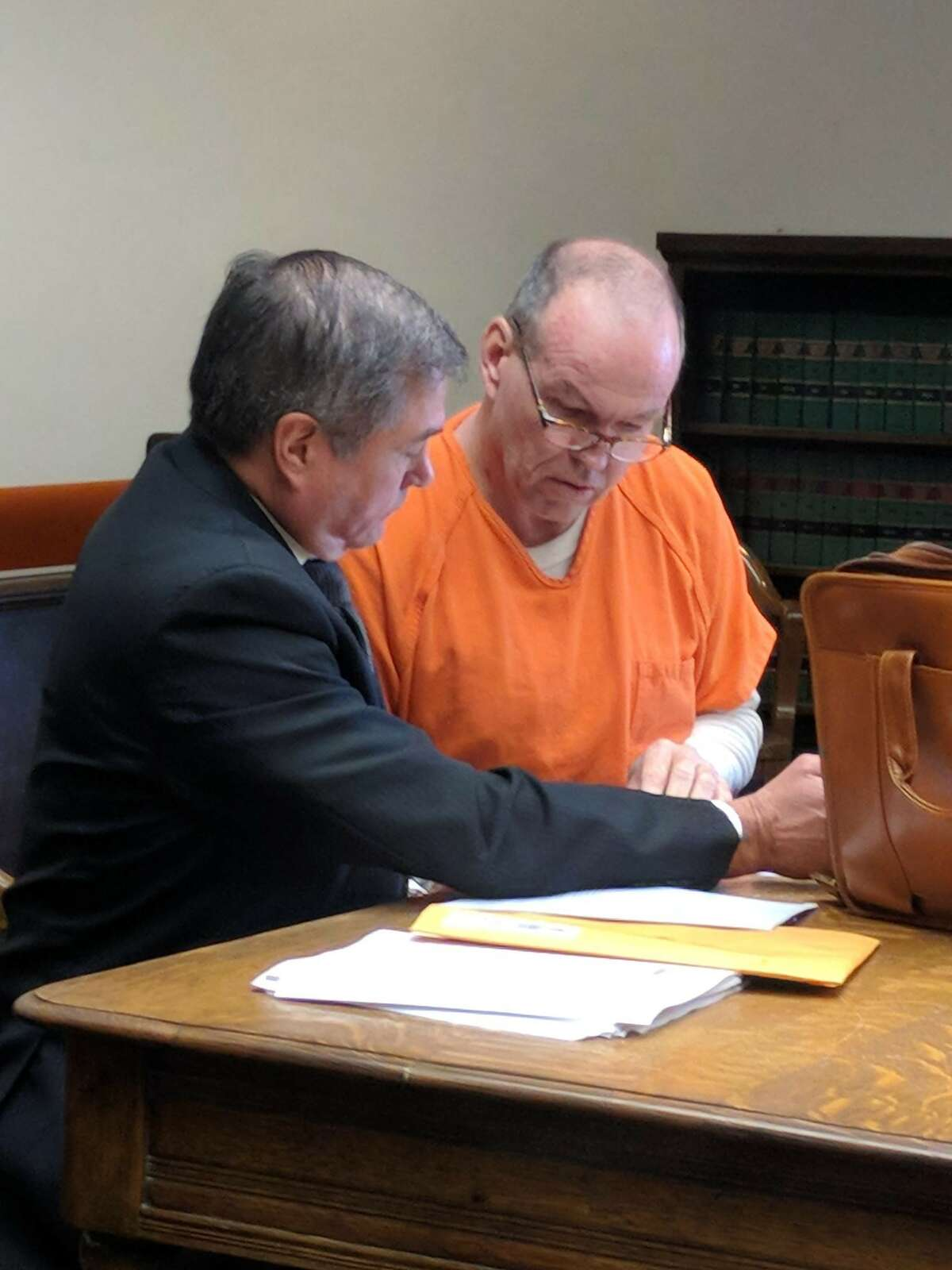 Greg Schirato, former deputy assistant director at the state Department of Fish and Wildlilfe, right, was sentenced to more than 10 years in prison Wednesday morning for breaking into the home of a co-worker in 2014 and raping her while she slept in her Olympia home. He signs documents after his sentencing with his attorney, Richard Woodrow.