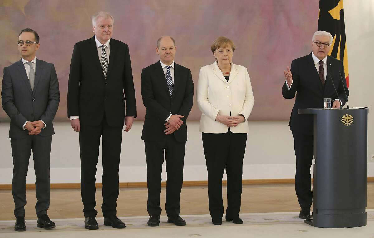 German president Frank-Walter Steinmeier, right, delivers a speech, next to chancellor Angela Merkel, second right, and her designated ministers, foreign minister Heiko Maas, left, interior minister Horst Seehofer, second left, and finance minister Olaf Scholz, during a ceremony for handing over the letters of appointment, in the presidential residence, Bellevue palace, in Berlin, Wednesday, March 14, 2018. (Wolfgang Kumm/dpa via AP)