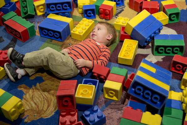 James Flade, 1 1/2, takes a break from playing with the big Lego blocks 03/14/18 at the DreamBuildGo Travel Adventure Lego exhibit at the Midland County Library Centennial Branch. Tim Fischer/Reporter-Telegram