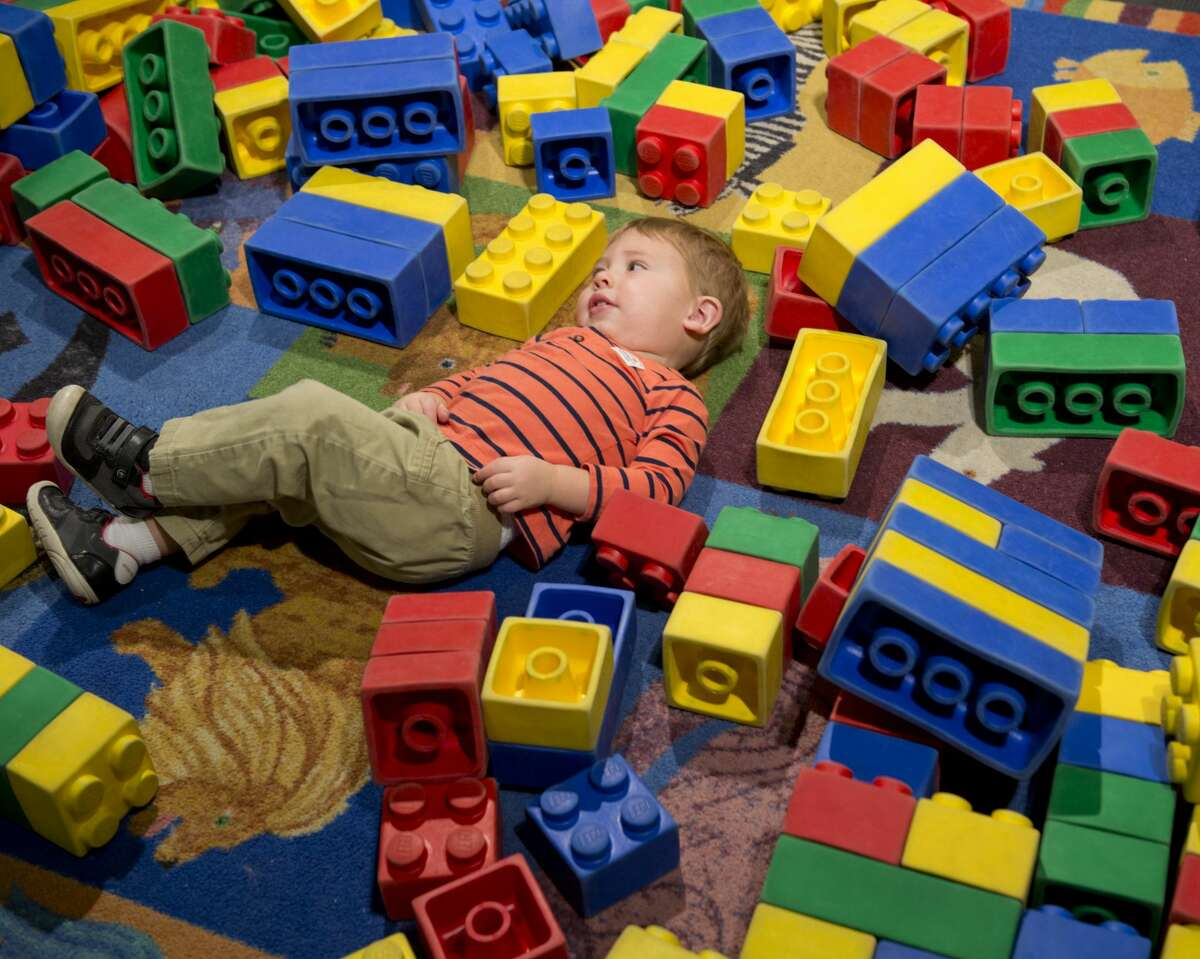 James Flade, 1 1/2, takes a break from playing with the big Lego blocks 03/14/18 at the DreamBuildGo Travel Adventure Lego exhibit at the Midland County Library Centennial Branch.The exhibit will be open till April 21.Tim Fischer/Reporter-Telegram