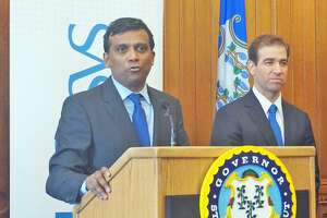 Infosys President Ravi Kumar (left) announced the creation of a new innovation and technology hub in Hartford at the Capitol in Hartford, Conn on Wednesday March 14, 2018, with Hartford Mayor Luke Bronin (right) and Governor Dannel P. Malloy.