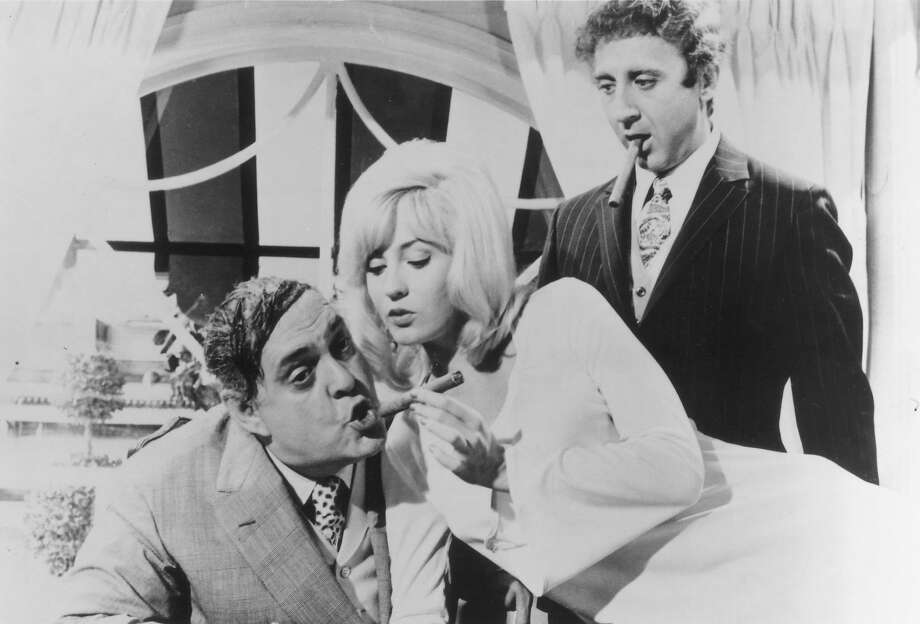 """Legendary Broadway producer Max Bialystock (Zero Mostel) puckers up for a cigar from secretary Ulla (Lee Meredith) as accountant Leo Bloom (Gene Wilder,  standing) looks on in Mel Brook's cult classic, """"The Producers."""" Photo: EMBASSY PICTURES C1987"""