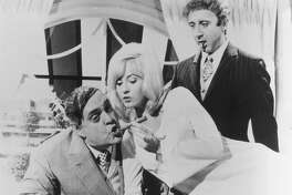 """THE PRODUCERS  (1967) - Legendary Broadway producer Max Bialystock (Zero Mostel) puckers up for a cigar from secretary Ulla (Lee Meredith) as accountant Leo Bloom (Gene Wilder,  standing) looks on in Mel Brook's cult classic, """"The Producers.""""   HOUCHRON CAPTION (05/10/1998):"""