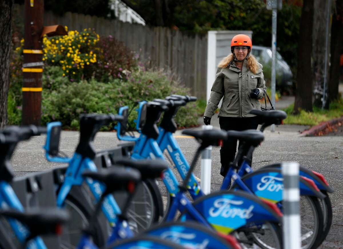 Wendy Wheeler arrives to undock a Ford GoBike in the Rockridge neighborhood for her three-mile commute by bicycle in Oakland, Calif. on Thursday, March 8, 2018. A few weeks back, Wheeler narrowly avoided an accident after discovering a vandal had cut the brake line on one of the shared bikes she was riding.