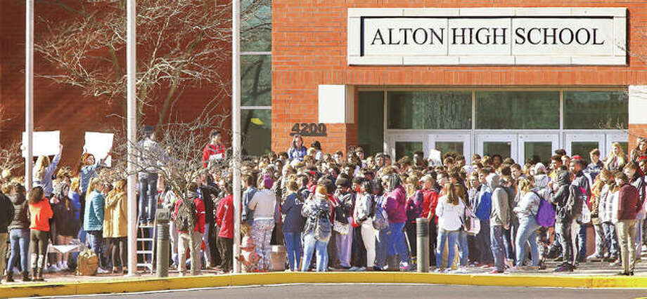Some of the hundreds of Alton High School students who walked out of classes Wednesday, on the one-month anniversary of the Parkland, Florida, school shooting that left 17 people dead, pause to hear the names of the 17 called out and observe three minutes of silence. The Alton School District superintendent did not allow press photographers on school property to cover the school-sanctioned walkout, which lasted about 20 minutes. Photo: John Badman | The Telegraph