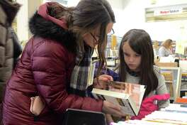 Melissa Balmer of Westport and her daughter, Tessa, 8, talk about a book at The Westport Library's Spring Book Sale, Saturday, March 10, 2018, in Westport, Conn.