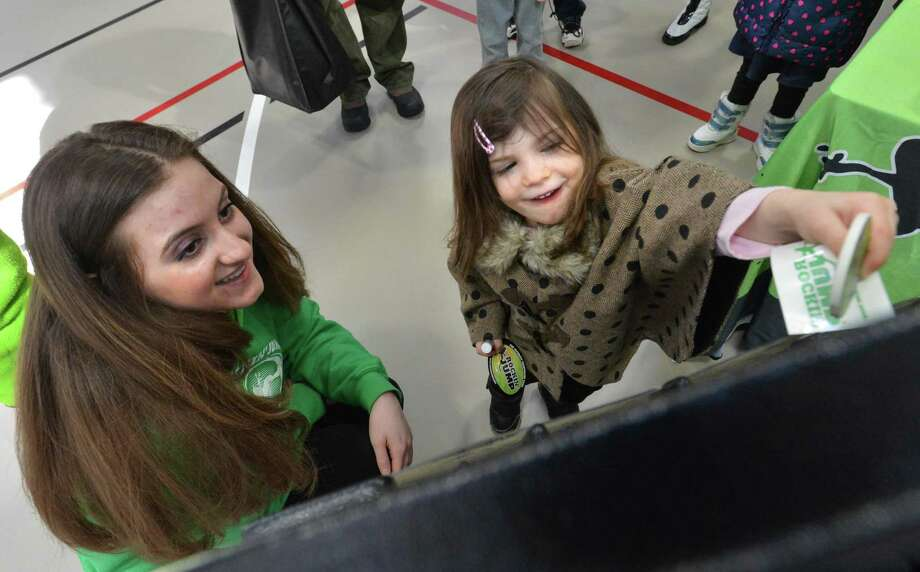 3 yr-old Emmi Appels from Fairfield trys her luck to get a free sticker or temporary tattoo with Celina Pozzuto at the Rockin' Jump Trampoline booth during the Fairfield Health and Fitness Expo, Sunday March 11, 2018 at Fairfield university in Fairfield Conn. Photo: Alex Von Kleydorff / Hearst Connecticut Media / Norwalk Hour