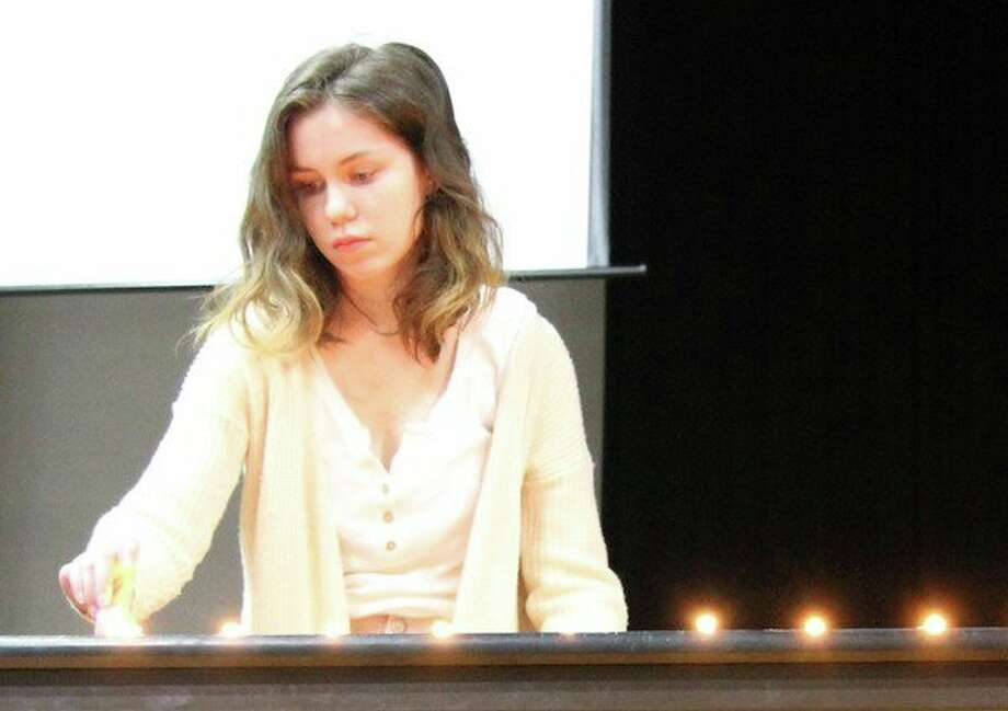 Caseville student Rebecca Morgan lights a candle during Wednesday's walkout assembly, where candles were lit in honor of each of the 17 victims who died in last month's school shooting in Parkland, Florida. (Submitted Photo)