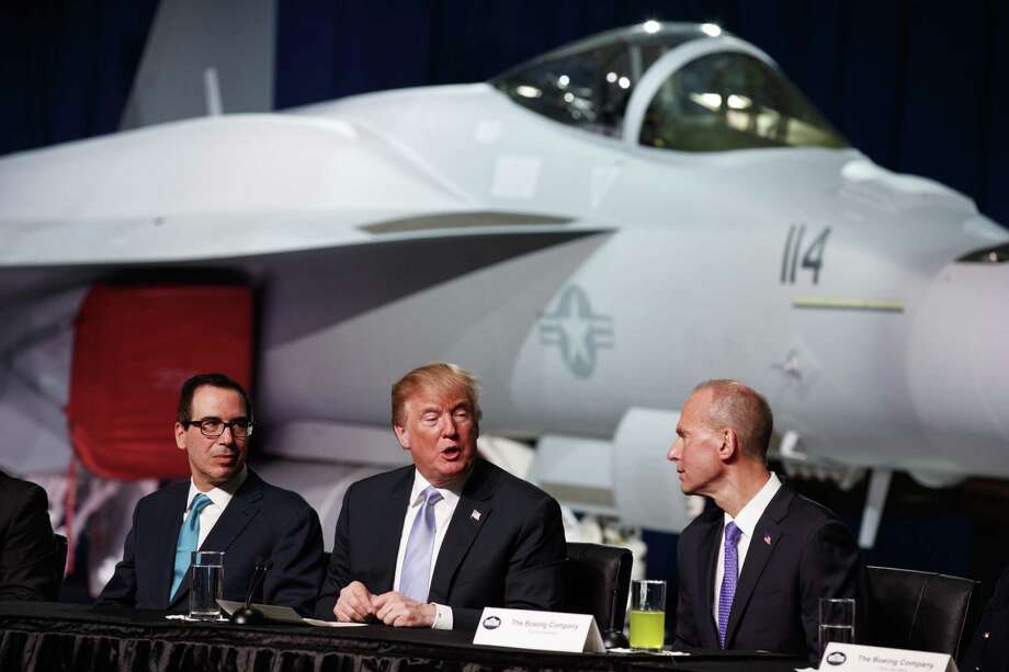 Treasury Secretary Steve Mnuchin (left) and Boeing CEO Dennis Muilenburg listen as President Donald Trump speaks during a roundtable discussion on tax policy at the Boeing Co., on Wednesday in St. Louis. Photo: Evan Vucci /Associated Press / Copyright 2018 The Associated Press. All rights reserved.