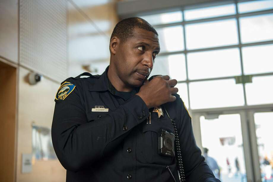 Officer Gary Lewis speaks into his lapel mic while on duty at Sylvester Greenwood Academy on Friday, March 9 2018. Photo: Rosa Furneaux, Special To The Chronicle