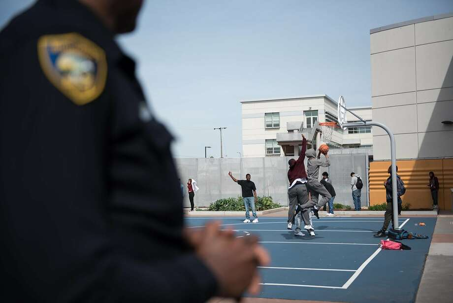 Students play basketball on the playground at Sylvester Greenwood Academy as Officer Gary Lewis stands watch on Friday, March 9 2018. Photo: Rosa Furneaux, Special To The Chronicle