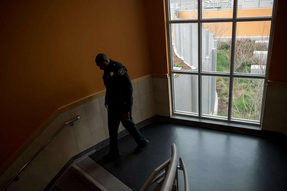 Joint caption: Officer Gary Lewis patrols the hallways at Sylvester Greenwood Academy on Friday, March 9 2018. 2nd pic: Officer Gary Lewis stands for a portrait outside Sylvester Greenwood Academy on Friday, March 9 2018. Photo: Rosa Furneaux, Special To The Chronicle