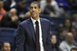 """FILE - In this Dec. 9, 2017 file photo, Connecticut head coach Kevin Ollie looks up at the scoreboard during the first half of an NCAA college basketball game against Coppin State in Storrs, Conn. UConn has fired Ollie, with the team under NCAA investigation and the Huskies having completed their second straight losing season. The university said in a statement Saturday, March 10, 2018,  it has """"initiated disciplinary procedures"""" to dismiss him for """"just cause."""" The school says it would have no further comment until its """"disciplinary process"""" and the ongoing NCAA inquiry are complete.  (AP Photo/Jessica Hill, File)"""