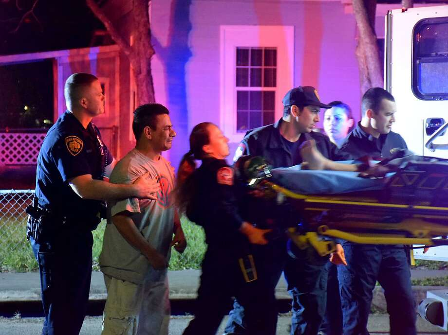 A relative of 14-year-old Andres Delgado IV is restrained as the boy was loaded into an ambulance Wednesday morning. The 14-year-old was struck in the torso by a bullet and was later pronounced dead. Photo: Caleb Downs /San Antonio Express-News / San Antonio Express-News