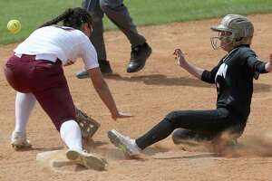 Edison's Mekiela Sibley slides Wednesday, March 14, 2018 into second base as Highlands' Alyssa Flores misses the throw. Sibley advanced to third base on the error. Edison won 6-2.