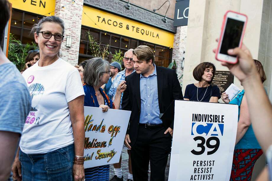 Demonstrator Barbara Sideri, center left, and former Democratic Congressional candidate Phil Janowicz, center right, speak outside the district office of Rep. Ed Royces in Orange County last August. Photo: Dania Maxwell, Special To The Chronicle