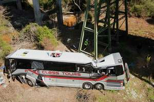 Emergency personnel walk around a bus that crashed into a ravine in Loxley, Ala., Tuesday, March 13, 2018. The bus carrying dozens of students and six adults from Channelview crashed early Tuesday on Interstate 10 nearly the Alabama-Florida line. The driver died and about three dozen others went to hospitals.