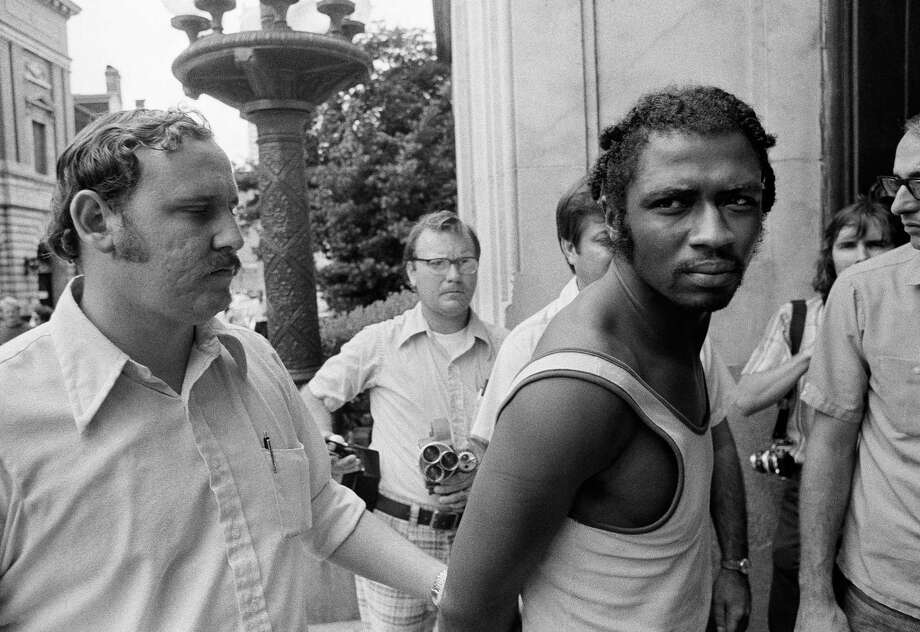 FILE- In this Sept. 1, 1973 file photo, Herman Bell, right, glares at the media following his arrest in New Orleans. The former member of the Black Liberation Army, who was convicted of fatally shooting two New York City police officers in 1971, has been granted parole and will be realized from Shawangunk Prison on April 17, 2018. (AP Photo) Photo: Anonymous / AP1973