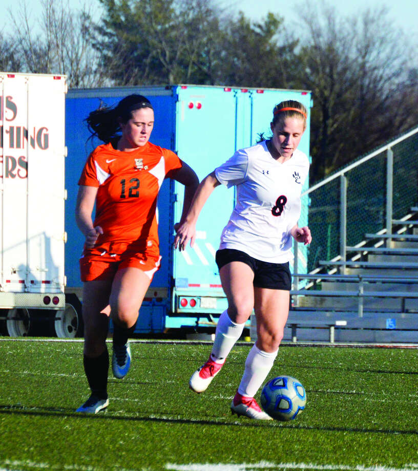 Edwardsville defender Sarah Kraus, right, dribbles away from a Waterloo attacker in the first half.