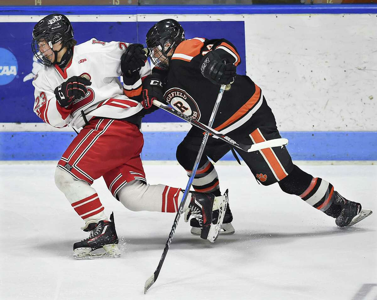 Fairfield Prep junior John Carroll battles Ridgefield junior Will Forrest in the CIAC Division I hockey semifinal matchup, Wednesday, March 14, 2018, at Ingalls Rink in New Haven. Prep won, 4-1.
