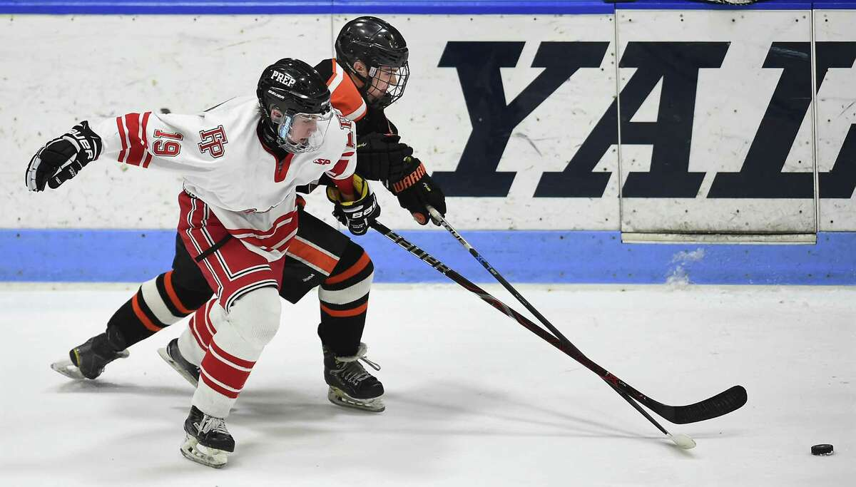 Fairfield Prep freshman Mason Whitney battles Ridgefield senior Del Irving in the CIAC Division I hockey semifinal matchup, Wednesday, March 14, 2018, at Ingalls Rink in New Haven. Prep won, 4-1.