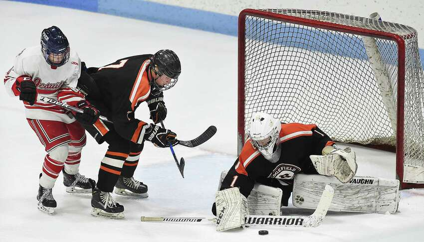 Fairfield Prep Calyb Reeves battles Ridgefield senior Liam Galloway at the goal as junior goalie Sean Gordon defends in the CIAC Division I hockey semifinal matchup, Wednesday, March 14, 2018, at Ingalls Rink in New Haven. Prep won, 4-1.
